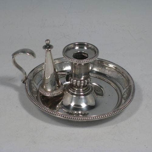 Antique Victorian sterling silver chamberstick for a taper candlestick, having a removable dunce-cap extinguisher, bead-edged borders, and hand-chased decoration on the pan sides. Made by George and Charles Fox of London in 1857. Diameter9 cms (3 inches), height 6 cms (2.25 inches).