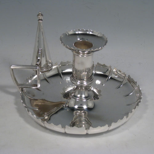 Antique Victorian silver plated chamberstick, having round base with shaped curved border, reeded handle, removable dunce-cap extinguisher, and removable bobeche. Made by William Hutton in ca. 1900. The dimensions of this hand-made silver plated chamberstick are diameter 15 cms (6 inches), width 15 cms (6 inches), and height 11.5 cms (4.5 inches).