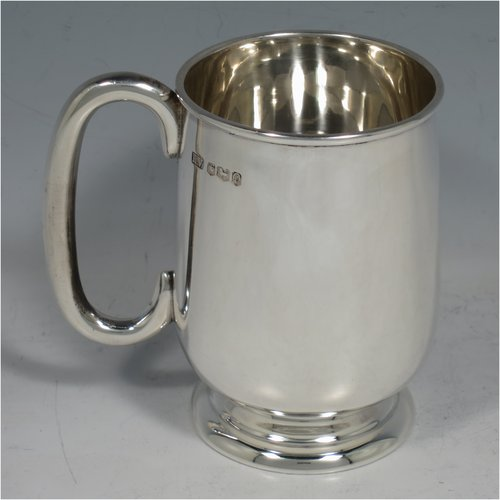 A Sterling Silver christening mug, having a plain round straight-sided body with tucked under belly, a scroll handle, and sitting on a collet foot. Made by Emile Viner of Sheffield in 1958. The dimensions of this fine hand-made silver christening mug are height 10 cms (4 inches), length 10 cms (4 inches), and it weighs approx. 205g (6.6 troy ounces).