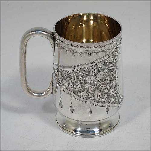 A very pretty Antique Victorian Sterling Silver christening mug, having a round body with straight tapering sights and tucked under belly, with hand-engraved floral and scroll-work decoration, a vacant oval cartouche, a plain loop handle, a gold-gilt interior, and all sitting on a pedestal foot. Made by Hilliard and Thomason of Birmingham in 1888. The dimensions of this fine hand-made antique silver christening mug are height 8.5 cms (3.3 inches), diameter at lip 5.5 cms (2.25 inches), and it weighs approx. 119g (3 troy ounces).