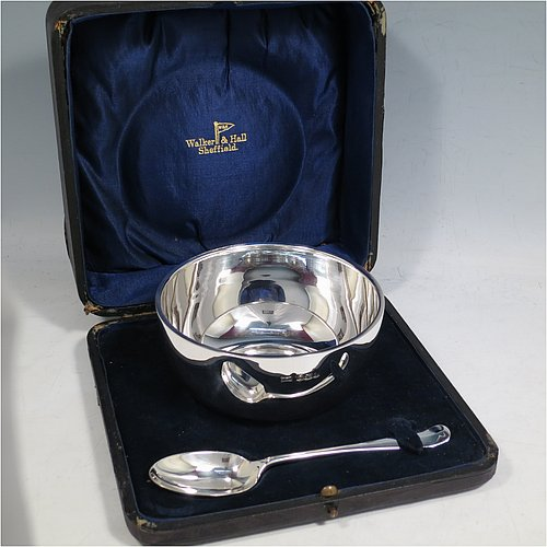 A Sterling Silver christening set, consisting of a plain round baluster bowl sitting on a flat base and a plain Hanoverian pattern spoon, all sitting in an original dark blue satin and velvet-lined presentation box. Made by Walker & Hall of Sheffield in 1931. The dimensions of this fine hand-made silver christening set are length of spoon 14 cms (5.5 inches), diameter of bowl 11 cms (4.3 inches), and the total weight is approx. 185g (6 troy ounces).