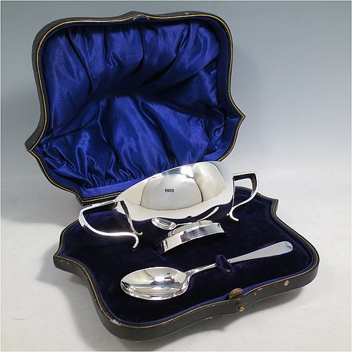 An Antique Sterling Silver christening set, consisting of a plain round Quaich-style bowl sitting on a collet foot and having two scroll side-handles, together with a plain Old English pattern spoon, all sitting in an original dark blue satin and velvet-lined presentation box. Made by William Hutton & Sons of Sheffield in 1912. The dimensions of this fine hand-made silver christening set are length of spoon 15 cms (6 inches), diameter of bowl 11 cms (4.3 inches), and the total weight is approx. 205g (6.6 troy ounces).