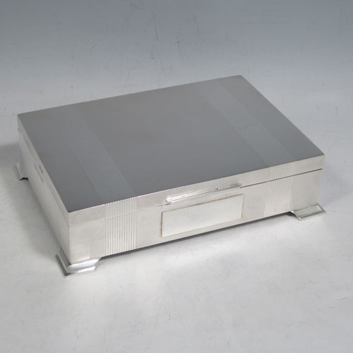 Sterling silver Art Deco style cigarette / cigar table box, having a very plain rectangular body with straight sides, hinged lid with thumb-piece, with engine-turned bands on inside border and lid, a wooden cedar-lined interior, and all sitting on four stepped corner feet. Made by J. B. Chatterley & Sons Ld., of Birmingham in 1955. The dimensions of this fine hand-made silver table box are length 17 cms (6.75 inches), height 6 cms (2.3 inches), and width 9.5 cms (3.75 inches).