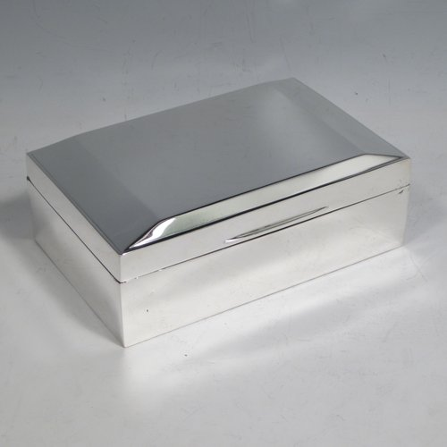 Sterling silver Art Deco style cigarette / cigar table box, having a very plain rectangular body, with a hinged lid having a panelled surface and thumb-piece, and a cedar wood-lined interior with removable divider. Made by Suckling Ltd., of Birmingham in 1953. The dimensions of this fine hand-made silver table box are length 14 cms (5.5 inches), width 9.5 cms (3.75 inches), and height 5 cms (2 inches).