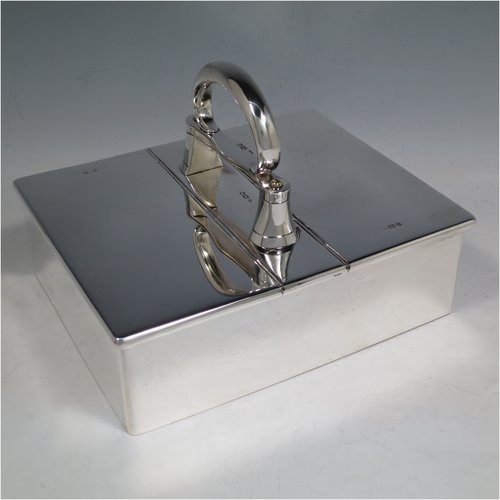 A Sterling Silver partners table cigar box, having a large plain rectangular body, with double hinged compartments opened by a mechanical carrying handle, and cedar wood-lined interiors. Made in London in 1933. The dimensions of this fine hand-made silver table cigar box are length 21 cms (8.25 inches), width 17 cms (6.75 inches), height inc. handle 14 cms (5.5 inches).