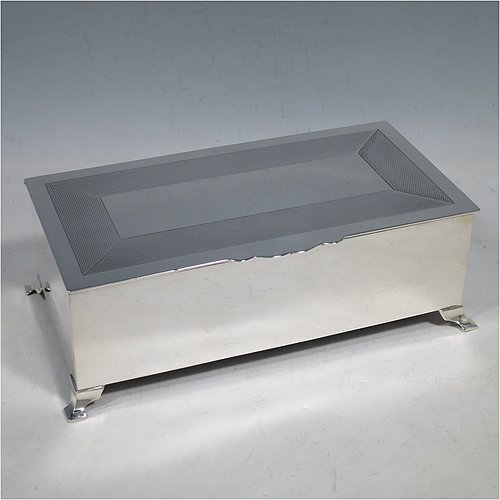 A Sterling Silver Art Deco style cigarette / cigar table box, having a very plain rectangular body with straight sides, a hinged lid with engine-turned decoration and thumb-piece, a wooden cedar-lined interior with divider, and all sitting on four stepped corner feet. Made by Mappin & Webb of London in 1929. The dimensions of this fine hand-made Art Deco silver table box are length 19 cms (7.5 inches), height 6 cms (2.5 inches), and width 10 cms (4 inches).