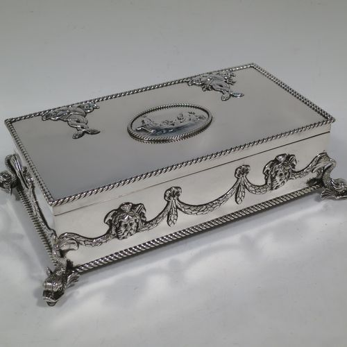 A very handsome and unusual Neptune themed Antique Victorian Sterling Silver cigar / cigarette box, having a rectangular body with applied rope-twist borders, laurel-leaf swags, Neptune face masks, and inter-twined dolphins, a hinged lid with an applied central oval cartouche with a scene of Neptune, mermaids, and sea-horses, a varnished wood-lined interior, and all sitting on four cast dolphin feet. Made by Reid and Sons of London in 1901. The dimensions of this fine hand-made antique silver table box are length 26 cms (10 inches), width 14 cms (5.5 inches), and height 8 cms (3 inches).