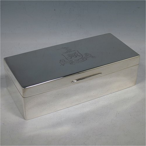 A Sterling Silver cigarette / cigar table box, having a plain rectangular body, with nice rounded corners, a hinged lid having an applied thumb-piece, and a gold-gilt and cedar wood-lined interior with two internal dividers. Made by Robert Comyns of London in 1932. The dimensions of this fine hand-made silver table box are length 19 cms (7.5 inches), width 9 cms (3.5 inches), and height 5.5 cms (2.25 inches). Please note that this item is crested.