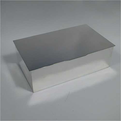 A large Sterling Silver cigarette or cigar table box, having a plain rectangular body, with angular corners, a hinged lid having a thumb-piece, and a gold-gilt and cedar wood-lined interior with two internal dividers. Made by Robert Comyns of London in 1937. The dimensions of this fine hand-made silver cigar or cigarette table box are length 23.5 cms (9.25 inches), width 14 cms (5 inches), and height 7 cms (2.75 inches).