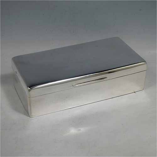 A Sterling Silver cigarette or cigar table box, having a plain rectangular body with nice rounded corners, a hinged lid having an applied thumb-piece, a gold-gilt interior to the lid, and a cedar wood-lined interior to the base, with a removable divider. Made by Alexander Clarke of London in 1925. The dimensions of this fine hand-made silver table box are length 17.5 cms (7 inches), width 9 cms (3.5 inches), and height 5 cms (2 inches).