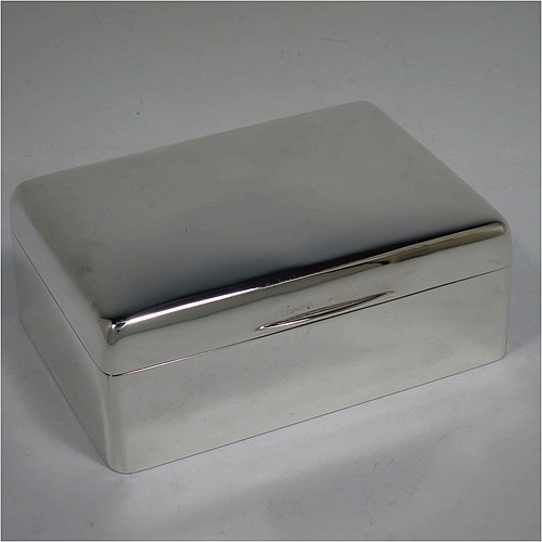 A handsome Antique Edwardian Sterling Silver cigarette / cigar table box, having a plain rectangular body with nice rounded corners, a hinged lid having an applied thumb-piece, and a cedar wood-lined interior to the base, with a removable divider. Made by Francis Higgins of London in 1905. The dimensions of this fine hand-made antique silver table cigar or cigarette box are length 13.5 cms (5.3 inches), width 9.5 cms (3.75 inches), and height 5.5 cms (2.25 inches).