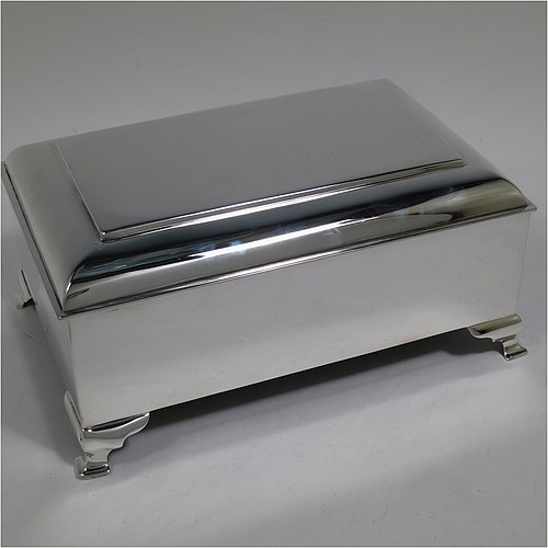 A large and very stylish Antique Edwardian Sterling Silver cigar / cigarette box, having a plain rectangular body, with a stepped and flat-topped hinged lid, a cedar wood-lined interior with internal divider, and all sitting on four cast stepped feet. Made by A. & J. Zimmerman of Birmingham in 1903. The dimensions of this fine hand-made antique silver table box are length 20 cms (8 inches), width 13.5 cms (5.25 inches), and height 9 cms (3.5 inches).