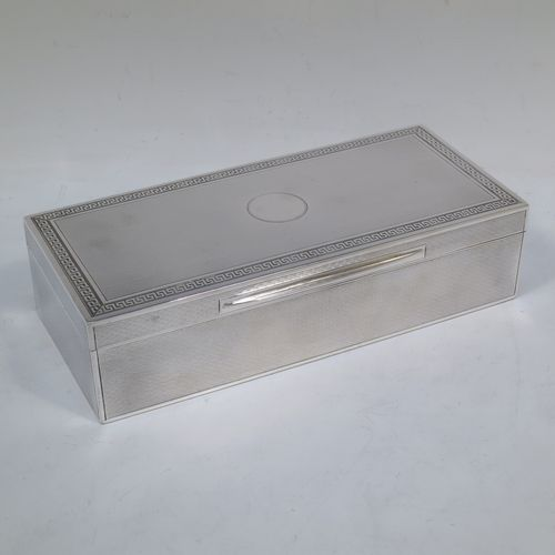 A very elegant Antique Sterling Silver cigarette / cigar table box, having a rectangular body with geometrically designed engine-turned decoration, a hinged lid with a central round vacant cartouche and a Greek-Key border, an applied thumb-piece, a gold-gilt and cedar wood-lined interior, and all sitting on a flat base. Made by Mappin and Webb of London in 1919. The dimensions of this fine hand-made antique silver table box are length 20 cms (8 inches), width 9 cms (3.5 inches), and height 5 cms (2 inches).