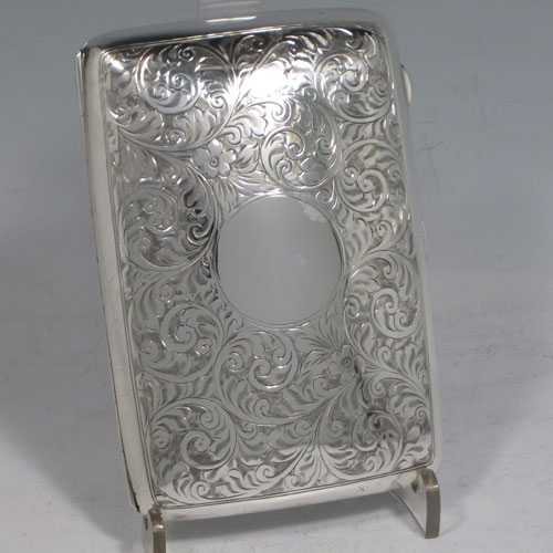 Sterling silver cigarette / cigarello case, having a rectangular shaped body with rounded edges, hand-engraved floral style decoration, central vacant cartouche, and thumb-piece with catch. Made by Henry Miller of Birmingham in 1921. The dimensions of this fine hand-made silver cigar case are length 11.5 cms (4.5 inches), width 8 cms (3 inches), depth 2.5 cms (1 inch), and the weight is approx. 147g (4.7 troy ounces).