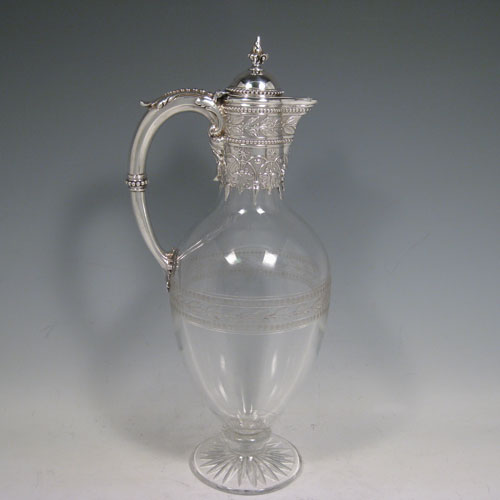 Antique Victorian sterling silver and hand-cut crystal claret jug, having a round crystal body with frosted cut decoration, a hand-chased mount with floral decoration, a hinged lid with cast finial, and a loop handle with beaded borders, all sitting on a pedestal foot. Made by the Robert Garrard of London in 1865. Height 32 cms (12.5 inches), length 15 cms (6 inches).