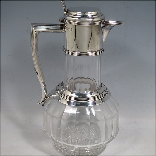 An Antique Victorian Silver Plated and hand-cut crystal claret jug, having a plain round mount with applied reeded borders, a stepped lid with a hand-pierced thumb-piece, a flat-topped scroll handle attached to a round and reeded security ring, together with a hand-cut round, panelled, and bellied crystal body with star-cut base. Made by William Hutton and Sons of Sheffield in 1880. The dimensions of this fine hand-made antique silver plated and crystal claret jug are height 24 cms (9.5 inches), and length 15 cms (6 inches).