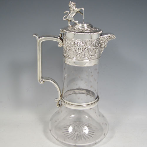 Antique Victorian sterling silver and hand-cut crystal claret jug, having a Bacchus mount with hand-chased grape-vine decoration, a hinged lid with cast rampant lion holding a shield, a hand-engraved scrolled handle with bead-edged attached ring, together with a hand-cut crystal body with frosted star-bursts. Made by Elkington & Co., of Birmingham in 1890. The dimensions of this fine hand-made silver and crystal claret jug are height 30 cms (11.75 inches), and length 17 cms (6.75 inches).