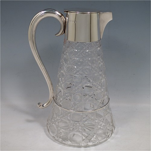 An Antique Edwardian Sterling Silver and hand-cut crystal claret jug, having a plain round mount, a hinged flat lid, a reeded scroll handle attached to a silver ring running around the main body, together with a hand-cut Hobnail pattern round body with straight tapering sides, and with a star-cut flat base. Made by Walker and Hall of Sheffield in 1909. The dimensions of this fine hand-made antique silver and crystal claret jug are height 24 cms (9.5 inches), and length 14 cms (5.5 inches).