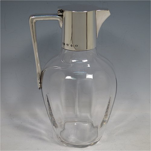 An Antique Victorian Sterling Silver and hand-cut crystal claret jug, having a plain round mount, with a flat hinged lid, a plain angular handle, and a cut-off sparrow-beak style spout, together with a hand-cut crystal body with slight panelling sitting on a flat base. Made by Elkington & Co., of Birmingham in 1897. The dimensions of this fine hand-made antique silver and crystal claret jug are height 21.5 cms (8.5 inches), and length 14 cms (5.5 inches).