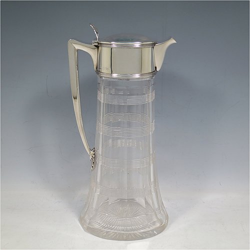 An Antique Edwardian Sterling Silver and hand-cut crystal claret jug, having a plain oval mount with reeded borders, a hinged slightly domed lid with a pierced thumb-piece, a plain handle with applied star end, together with a hand-cut oval and panelled crystal body with reeded bands and star-cut base. Made by John Grinsell & Sons of London in 1900. The dimensions of this fine hand-made antique silver and crystal claret jug are height 27 cms (10.75 inches), and length 13 cms (5 inches).
