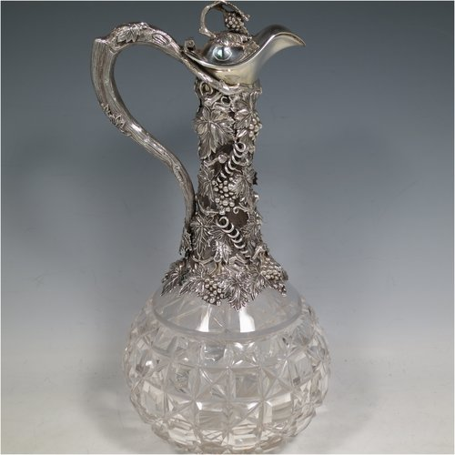 An Antique Victorian Sterling Silver and hand-cut crystal claret jug, having a cast grape and vine leaf mount on a hobnail-cut crystal round baluster body. with cast scroll vine tendril handle, a hinged lid with cast finial, and sitting on a flat star-cut base. Made by Cartwright & Woodward of Birmingham in 1860. The dimensions of this fine hand-made antique silver and crystal claret jug are height 31 cms (12.25 inches), and diameter at base 14 cms (5.5 inches).
