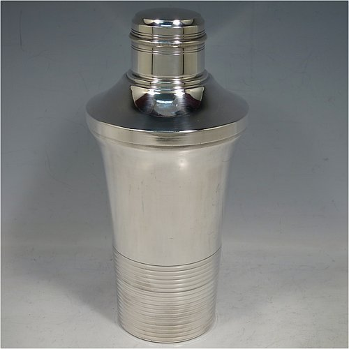 A very handsome Art Deco style Silver-Plated cocktail shaker, having a plain round body with tapering sides, with a pull-off lid and a strainer section, together with a lower band of hand-chased reeded decoration. Made in ca. 1930. The dimensions of this fine hand-made silver plated cocktail shaker are height 21 cms (8.25 inches), diameter at widest point 10 cms (4 inches).