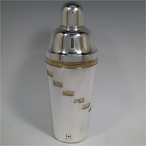 A rare and unusual Silver-Plated Art Deco mechanical menu cocktail shaker, having a plain round body with tapering sides, with a pull-off lid and strainer section, with an internal revolving gold-plated menu system showing various cocktails on the upper menu and then all the required constituents in small staggered windows down the body. Made in ca. 1930. The dimensions of this fine hand-made silver plated menu cocktail shaker are height 27 cms (10.75 inches), diameter at widest point 10 cms (4 inches).