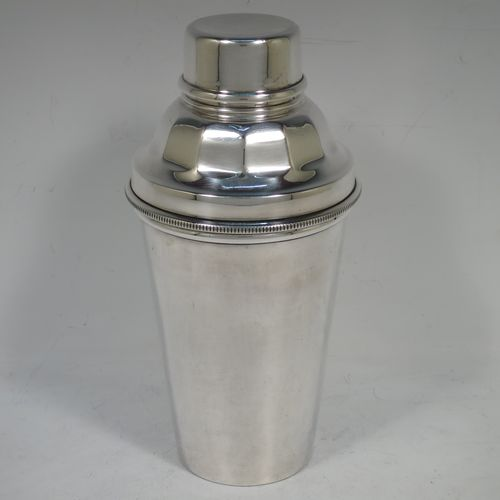 A handsome Silver-Plated Art Deco cocktail shaker, having a plain round body with tapering sides, with a pull-off lid and panelled strainer section, and an applied knurled edge to the main body. Made by Docker and Burn Ltd., of Sheffield in ca. 1930. The dimensions of this fine hand-made silver plated cocktail shaker are height 19 cms (7.5 inches), diameter at widest point 9 cms (3.5 inches).
