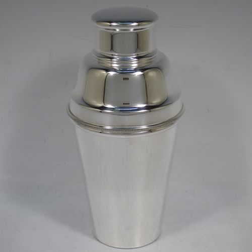A handsome Silver-Plated Art Deco cocktail shaker, having a plain round body with tapering sides, with a pull-off lid, and strainer section with an applied knurled edge, and the main body with a flat base. Made in Sheffield, England, in ca. 1930. The dimensions of this fine hand-made silver plated cocktail shaker are height 19 cms (7.5 inches), diameter at widest point 9 cms (3.5 inches).