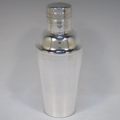 A handsome Silver-Plated Art Deco cocktail shaker, having a plain round body with tapering sides, with a reeded and engine-turned pull-off lid, and a central removable strainer section. Made by Elkington and Co., of Sheffield in ca. 1930. The dimensions of this fine hand-made silver plated cocktail shaker are height 21.5 cms (8.5 inches), and diameter at widest point is 9 cms (3.5 inches).