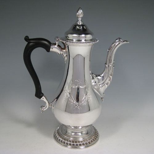 Antique Georgian sterling silver baluster style large coffee pot with gadroon edges, wooden scroll handle, flame knop finial, and anthemion leaf decorated spout. Made by Francis Butty and Nicholas Dummee of London in 1772. Height 30 cms (11.75 inches), length 21.5 cms (8.5 inches). Weight approx. 28 troy ounces (868g). Please note that this item is crested on both sides of the main body.
