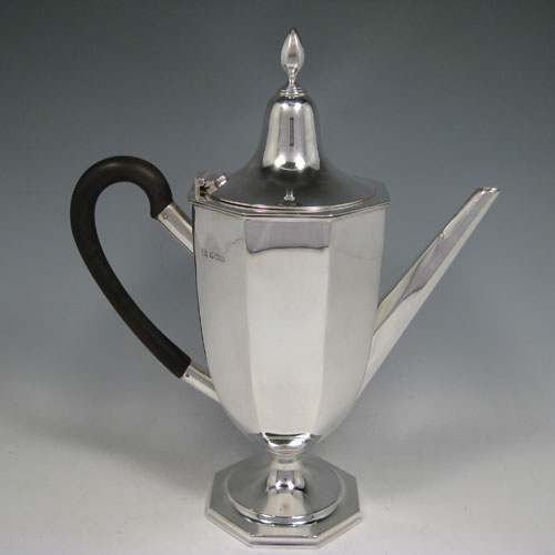A Sterling Silver large sized fine hand-made panelled coffee pot with plain panelled body, a hinged lid with finial, a curved wooden handle, and all sitting on a pedestal foot. Made by William Bush of Sheffield in 1932. The dimensions of this fine silver coffee pot are length 24 cms (9.5 inches), height 29 cms (11.5 inches), and it weighs approx. 682g (22 troy ounces).