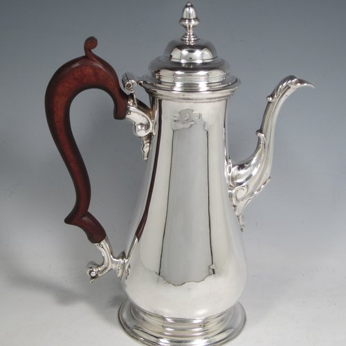 Antique Georgian sterling silver coffee pot, having a plain round baluster body, a domed hinged lid with acorn finial, a scroll spout, and a scrolled wooden handle, sitting on a round pedestal foot. Made by John Mackfarlen (Poss.) of London in 1759. The dimensions of this fine hand-made silver coffee pot are length 20 cms (8 inches), height 26 cms (10.25 inches), and it weighs approx. 800g (26 troy ounces).
