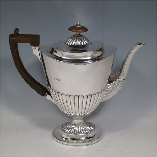 An Antique Victorian Sterling Silver coffee pot, in a Queen Anne style, having an oval tapering body with hand-chased half-fluted decoration, a wooden handle, a hinged lid with an invisible flat hinge and wooden finial, and all sitting on a pedestal foot. Made by Charles Stuart Harris of London in 1885. The dimensions of this fine hand-made antique silver coffee pot are length 22 cms (8.5 inches), height 21 cms (8.25 inches), and it weighs approx. 340g (11 troy ounces).