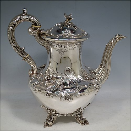 An Antique Georgian William IV Sterling Silver hand-chased coffee pot, having a round hand-chased bellied body with floral and scroll decoration, a hinged lid with original cast flower finial, an insulated silver handle with anthemion thumb-piece, and sitting on cast floral and scroll feet. Made by the Barnard Brothers of London in 1832. The dimensions of this fine hand-made antique silver coffee pot are height 25 cms (9.75 inches), length 25.5 cms (10 inches), and it weighs approx. 978g (31.5 troy ounces).