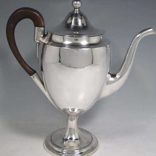 Antique Georgian sterling silver coffee pot, having a plain round body with tapering sides, a pull-off domed lid with ball finial, a scroll spout, and a scrolled wooden handle, sitting on an oval pedestal foot. Made by Thomas Lamborn of Sheffield in 1798. The dimensions of this fine hand-made silver coffee pot are length 25.5 cms (10 inches), height 27 cms (10.6 inches), and it weighs approx. 590g (19 troy ounces).