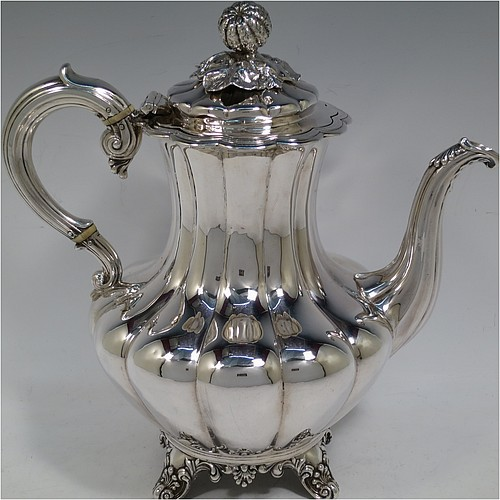A very handsome Antique Victorian Sterling Silver hand-chased coffee pot, having a round hand-chased baluster body with melon-style fluting, a hinged lid with melon fluting and original cast floral finial, an insulated silver handle, a fluted spout, and all sitting on four shell and scroll feet. Made by the Savoury Brothers of London in 1846. The dimensions of this fine hand-made antique silver coffee pot are height 26 cms (10.25 inches), length 26 cms (10.25 inches), and it weighs approx. 862g (28 troy ounces).