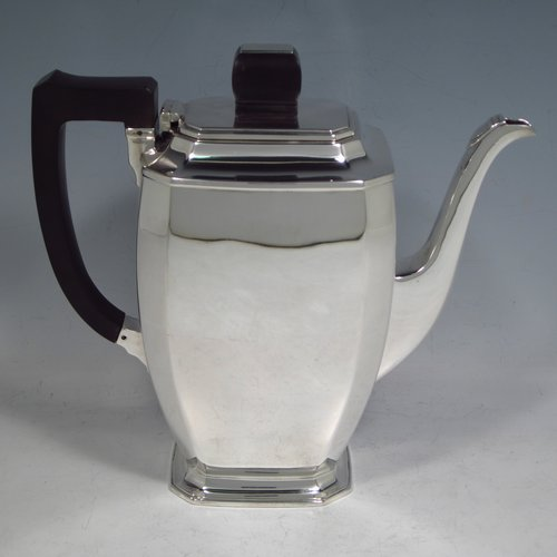 A Sterling silver Art Deco style coffee pot, having very plain panelled body with tapering sides, a wooden handle, a hinged lid with matching finial, and all sitting on a collet foot. Made by Mappin & Webb of Sheffield in 1950. The dimensions of this fine hand-made silver coffee pot are length 20 cms (8 inches), height 19 cms (7.5 inches), and it weighs approx. 600g (19.4 troy ounces).