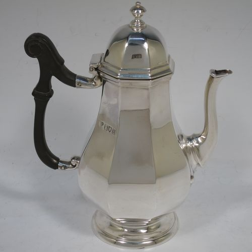 A handsome Antique Sterling Silver small coffee pot for two people, having a plain panelled and bellied body, with a black wooden scroll handle, a hinged and panelled domed lid with cast finial, and all sitting on a pedestal feet. Made by the Goldsmiths & Silversmiths of London in 1913. The dimensions of this fine hand-made antique sterling silver small coffee pot are height 17 cms (6.75 inches), length 14.5 cms (5.75 inches), and it weighs approx. 250g (8 troy ounces).