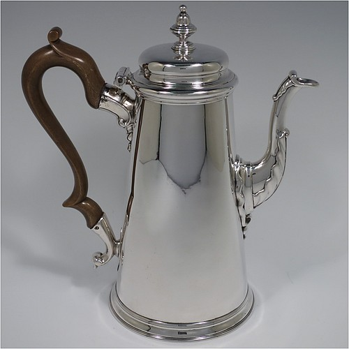 An Antique Georgian Sterling Silver George II coffee pot, having a plain round body with straight tapering sides, a hinged cushion style lid with cast finial, a curved spout with an applied anthemion leaf, a hand-carved wooden scroll handle, and all sitting on a collet foot. Made by Edward Vincent of London in 1738. The dimensions of this fine hand-made antique silver coffee pot are length 21 cms (8.25 inches), height 23.5 cms (9.25 inches), and it weighs approx. 845g (27 troy ounces). Please note that this item is engraved with a full armorial crest on one side.