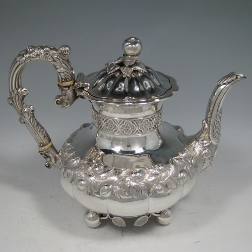 Antique Georgian sterling silver hand-chased coffee pot, having a round hand-chased baluster body with floral decoration, a hinged lid with melon fluting and original cast finial, an insulated silver handle, and sitting on four ball feet with applied cast leaves. Made by one of the most important English silversmiths from the late Georgian period, Edward Farrell, of London in 1828. The dimensions of this fine hand-made silver coffee pot are height 21 cms (8.25 inches), length 25.5 cms (10 inches), and it weighs approx. 930g (30 troy ounces).
