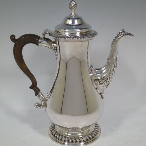 A very handsome Antique Georgian Sterling Silver coffee pot, having a plain round bellied body, with applied gadroon borders, a wooden scroll handle, a flame knop finial, and anthemion leaf decorated spout. Made by William Grundy London in 1775. The dimensions of this fine hand-made antique silver coffee pot are height 26 cms (10.25 inches), length 22 cms (8.75 inches), and it weighs approx. 800g (25.8 troy ounces).