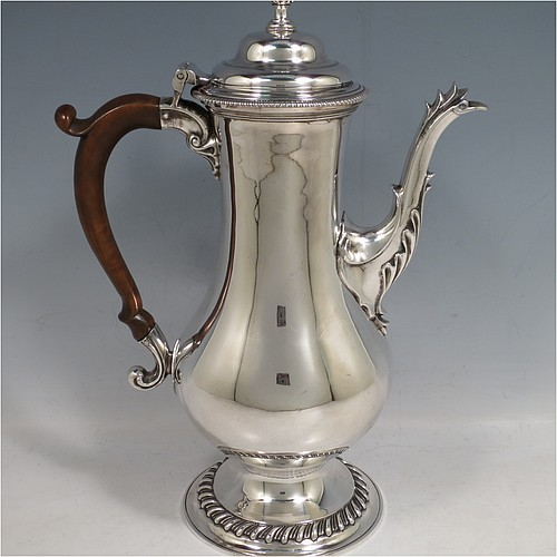 An Antique Georgian Sterling Silver coffee pot, having a plain round bellied body, with applied gadroon borders, a wooden scroll handle, a flame knop finial, and anthemion leaf decorated spout. Made in London in 1774. The dimensions of this fine hand-made antique silver coffee pot are height 30.5 cms (12 inches), length 22 cms (8.75 inches), and it weighs approx. 850g (27.4 troy ounces).