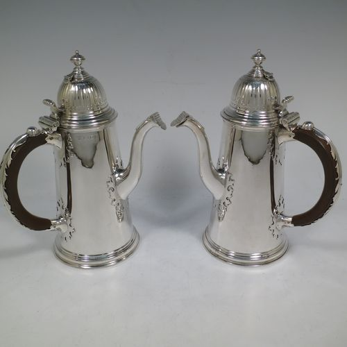 A very unusual and fine pair of Sterling Silver Queen Anne style side-handled coffee or chocolate pots, having plain round bodies with straight tapering sides and applied cut-card work, hinged domed lids with cast thumb-pieces and hinged finials to allow the use of a chocolate stirring spoons, curved spouts with hinged openings, hand-carved wooden scroll handles with applied silver mounts, and all sitting on round collet feet. Made by Heming and Co., of London in 1932. The dimensions of this fine hand-made pair of silver chocoloate or coffee pots are length 16.5 cms (6.5 inches), height 23 cms (9 inches), and they weigh a total of approx. 1,302g (42 troy ounces).