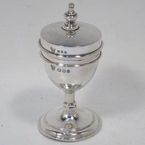 A handsome and unusual Antique Sterling Silver two-piece travelling communion set consisting of a chalice body for consecrated wine, together with lift-off pyx box with cover lid for host wafers. The lid with an applied urn-shaped finial, and the pyx body having a gold-gilt interior. Made by Charles Boyton and Sons of London in 1918. The dimensions of this fine hand-made antique silver travelling communion set are height 10 cms (4 inches), diameter of main body 4.5 cms (1.75 inches), and it weighs approx. 92g (3 troy ounces).