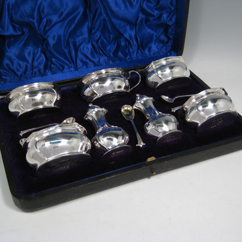 Antique Victorian sterling silver Art Nouveau seven-piece condiment service with spoons, all in original satin and velvet-lined presentation box. Consisting of four open salt cellars with gold-gilt interiors, two pepper pots with pull-off lids, and a single mustard pot with hinged lid and gold-gilt interior, together with four salt spoons and one mustard spoon with gold-gilt bowls. All made by James Round of Sheffield in 1897 (the condiment spoons are made by James Round in 1901). Length of mustard pot 9 cms (3.5 inches), height of pepper pots 9 cms (3.5 inches). Total weight approx. 13 troy ounces (403 g).