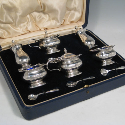 Sterling silver six-piece baluster condiment set in original satin and velvet-lined presentation box, having two open salts and two covered mustard pots all with blue-glass liners, two pepper pots, and four silver condiment spoons. Made by mappin and Webb of Birmingham in 1935. Height of pepper pots 8 cms (3 inches), length of mustard pots 7 cms (2.75 inches). Total weight approx. 232g (7.5 troy ounces).