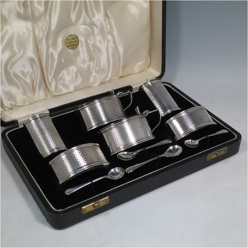 A Sterling Silver Art Deco condiment service, having oval straight-sided bodies with engine-turned decoration, with original blue-glass liners, pull-off lids on the peppers, hinged lids on the mustards, and all in original velvet and satin-lined presentation box. Consisting of two mustard pots, two pepper pots, two salt cellars, and four condiment spoons. Made in Chester and Birmingham from 1930 to 1934. Height of peppers 6.5 cms (2.5 inches), length of mustard 8 cms (3 inches), and a total weight of approx. 248g (8 troy ounces).