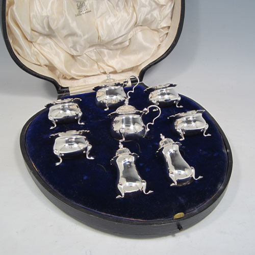 Antique sterling silver eight-piece condiment set, consisting of four open salt cellars with blue-glass liners, two mustard pots with hinged lids, and two pepper shakers, all with plain baluster round bodies, chippendale borders, and sitting on four cabriole legs, and all fitted into an original satin and velvet-lined presentation box. Made by Robert and William Sorely pf London in 1911. The dimensions of this fine hand-made silver condiment service are height of pepper pots 7 cms (2.75 inches), length of mustard pots 7 cms (2.75 inches), and with a total weight of approx. 252g (8 troy ounces).