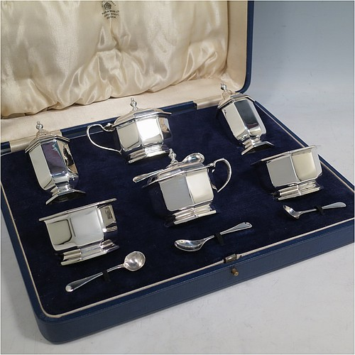 A Sterling Silver Art Deco six-piece condiment service in a plain octagonal panelled style, consisting of two covered mustard pots with blue-glass liners, two open salts with blue-glass liners, two pepper shakers with pull-off lids, and four condiment spoons, all in their cream satin & dark blue velvet-lined presentation box. Made by Mappin & Webb of Birmingham in 1931. The dimensions of this fine hand-made silver condiment service are height of peppers 8 cms (3.25 inches), length of mustard pot 7.5 cms (3 inches), with a total weight of approx. 260g (8.4 troy ounces).